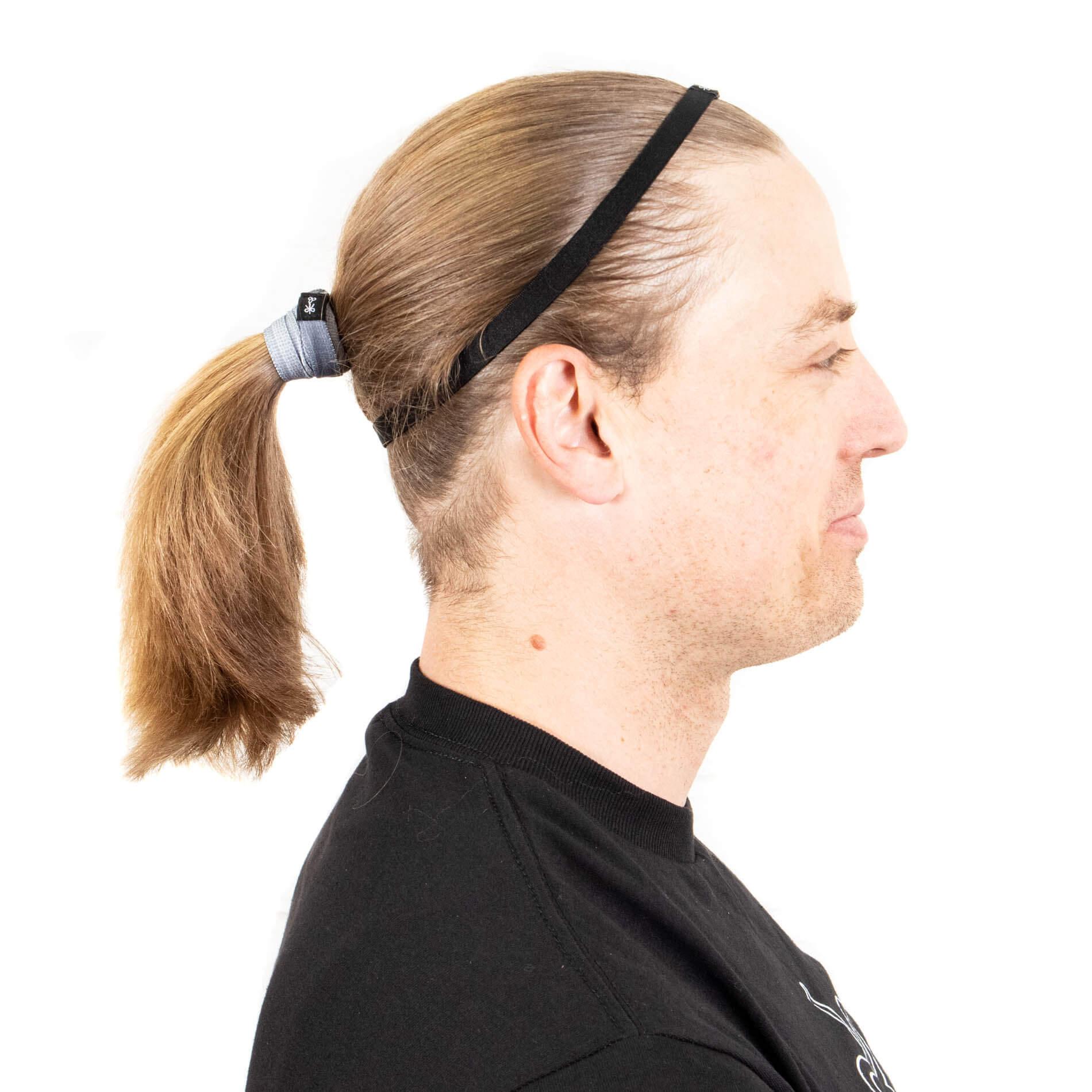 Thin headband on top of head with pony tail.