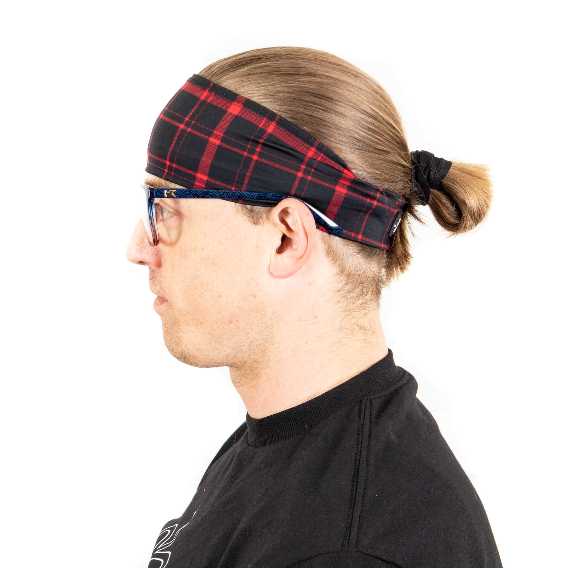 The Lumberman headband from The Longhairs under a man bun with knockaround sunglasses on.