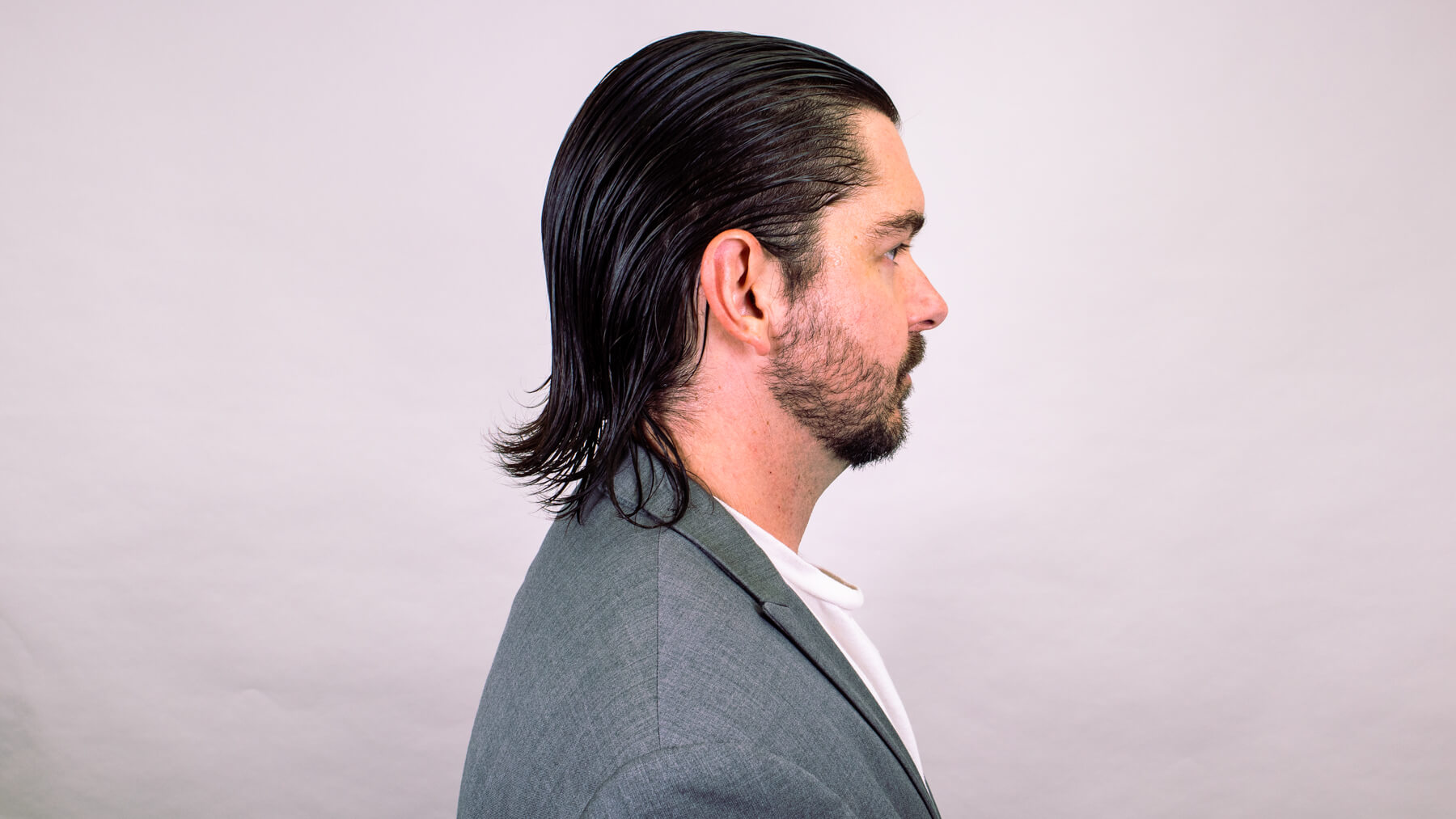 Slick back awkward stage hairstyle side profile view