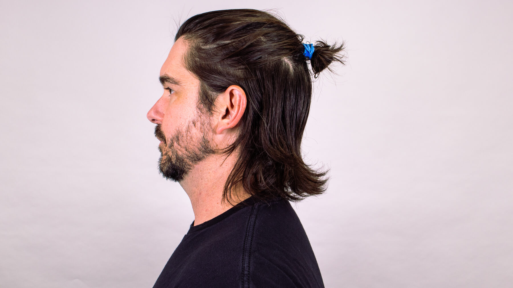 Top knot with awkward stage hairstyle side profile view