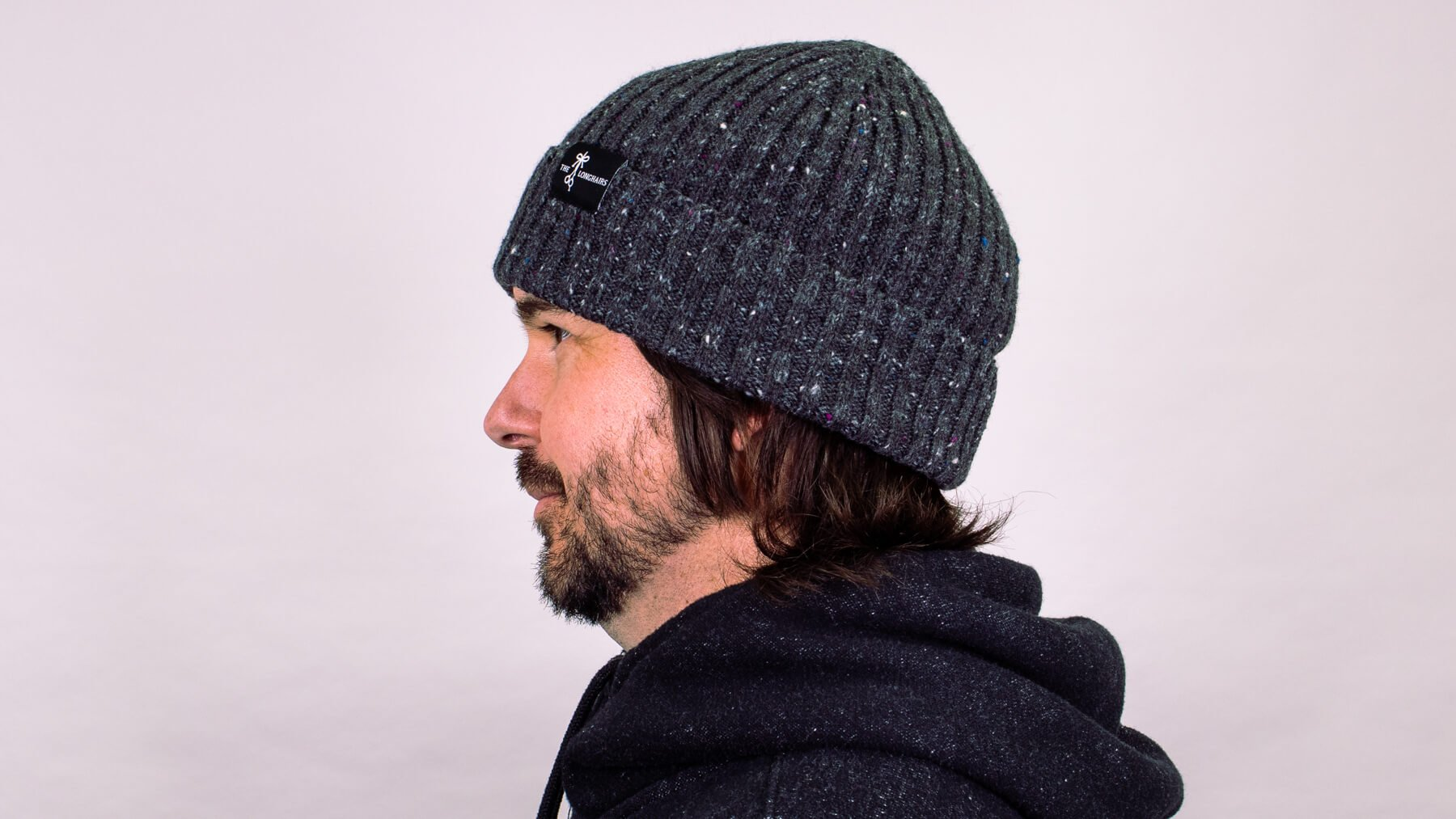 Beanie with awkward stage hairstyle side profile view