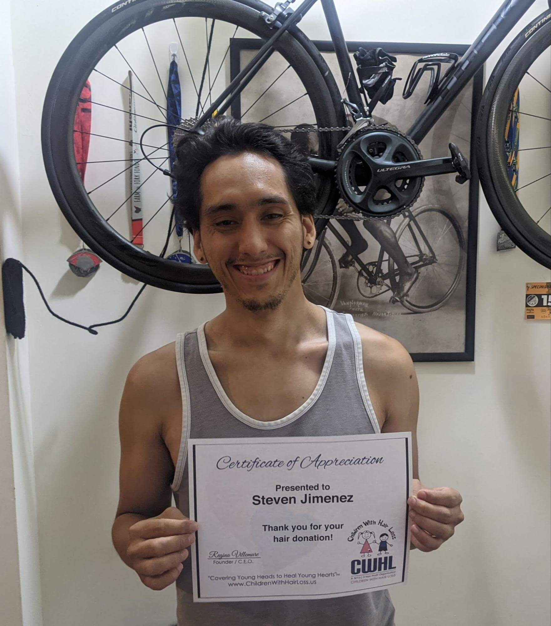 Steven holding his certificate from Children With Hair Loss