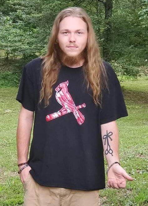 Austin Jackson standing outside flashing his forearm tattoo of The Longhairs logo
