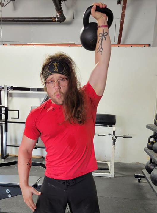 Brian Morehouse holding a 50lb kettle bell overhead and displaying his bound shears tattoo of The Longhairs logo