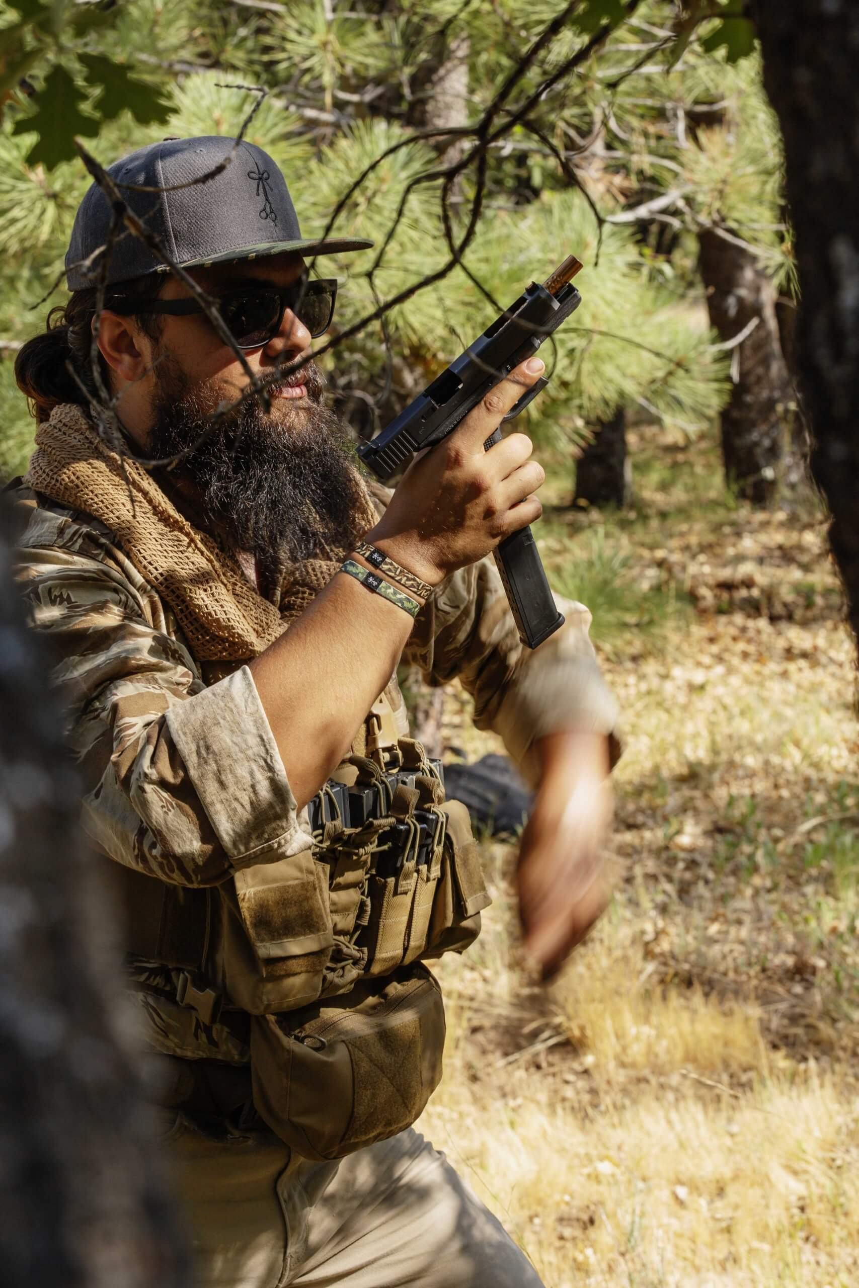 El Sicario in the woods reloading his 9mm during the camping trip photo shoot